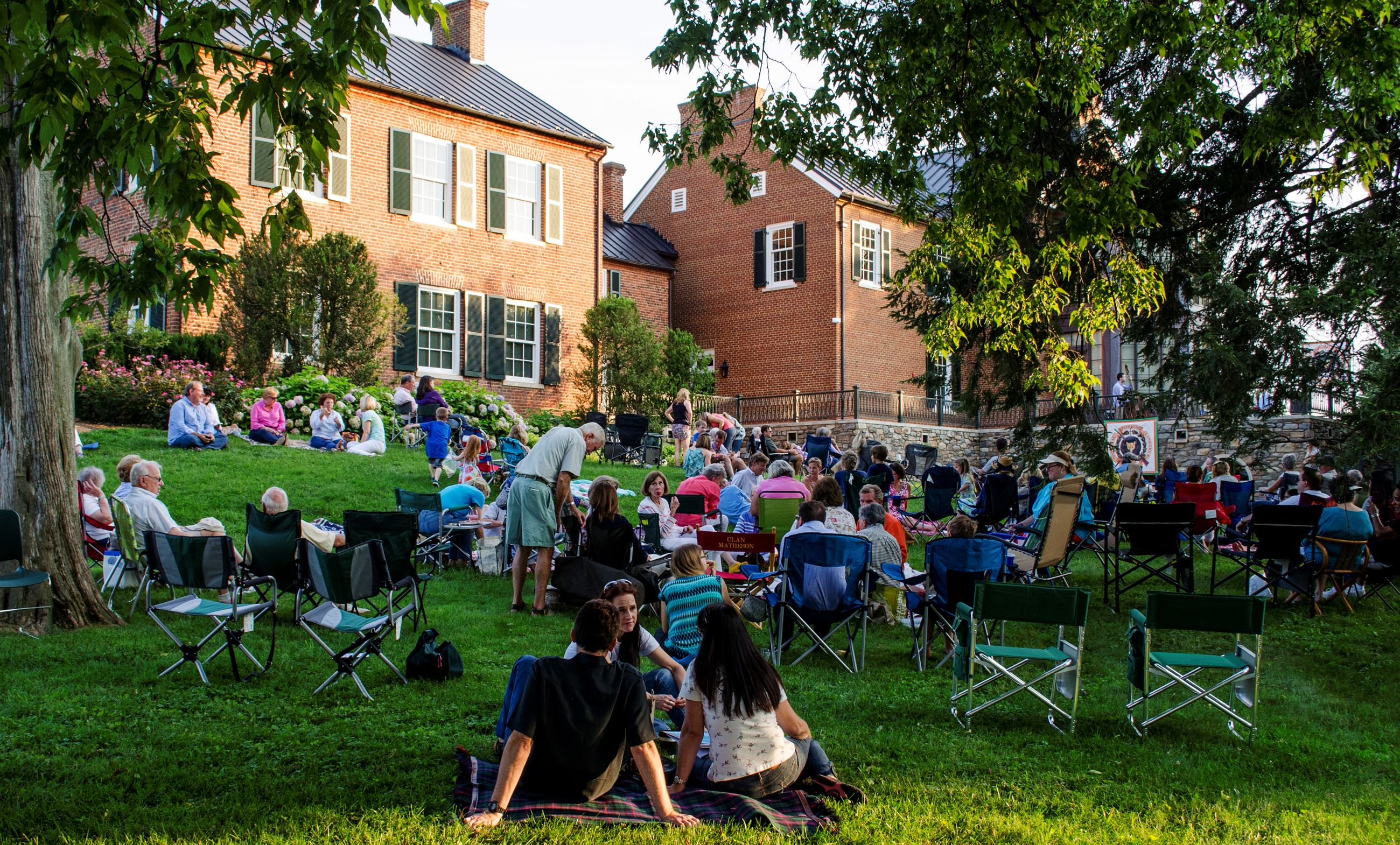 Open Late Concert goers sitting on the lawn